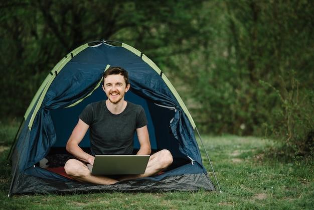 Mens die aan laptop in tent in aard werkt