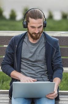 Mens die aan laptop met hoofdtelefoons in openlucht werkt