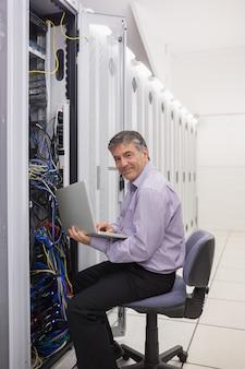 Mens die aan laptop werkt om servers te controleren
