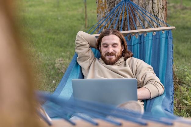 Mens die aan laptop werkt terwijl het zitten in hangmat