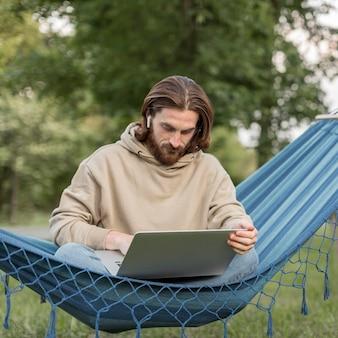 Mens die aan laptop werkt terwijl in hangmat