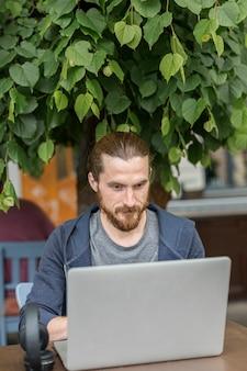 Mens die aan laptop werkt terwijl uit in de stad