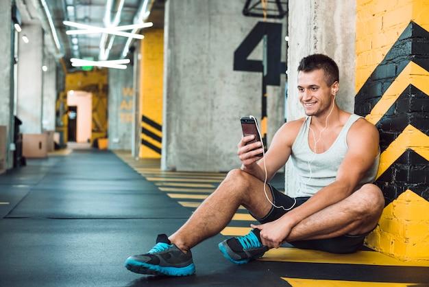 Mens die aan muziek op cellphone in gymnastiek luistert