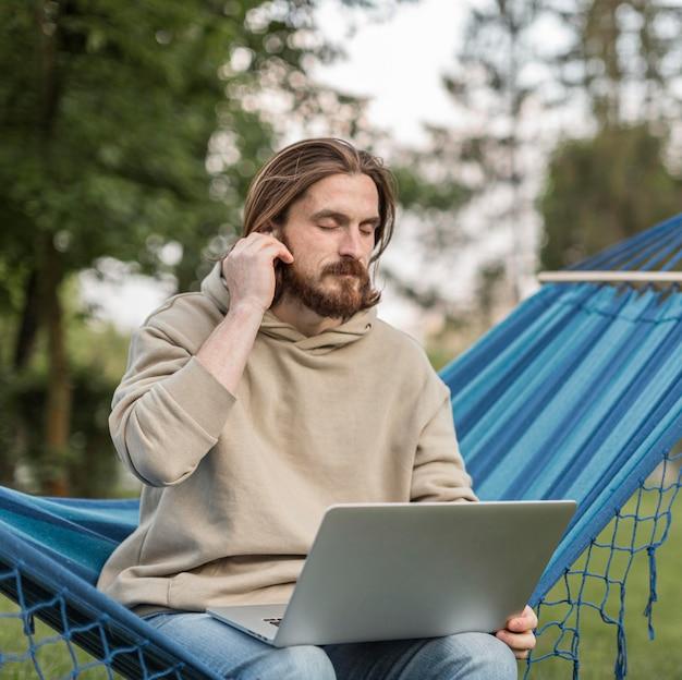 Mens die aan muziek op hangmat met laptop luistert