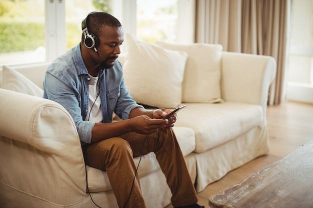 Mens die aan muziek op mobiele telefoon in woonkamer luistert