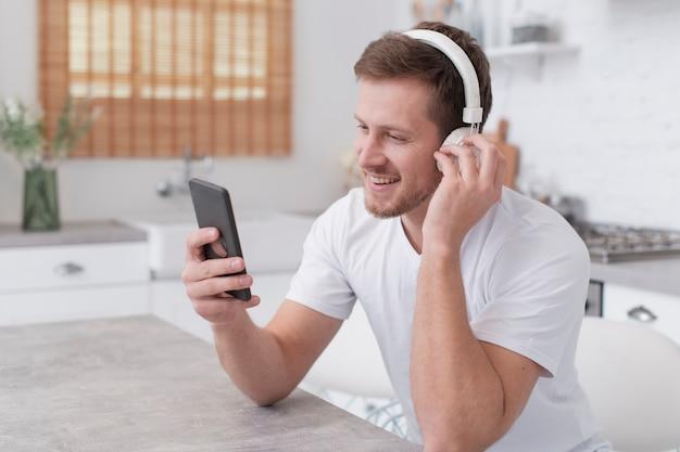 Mens die aan muziek op witte hoofdtelefoons luistert