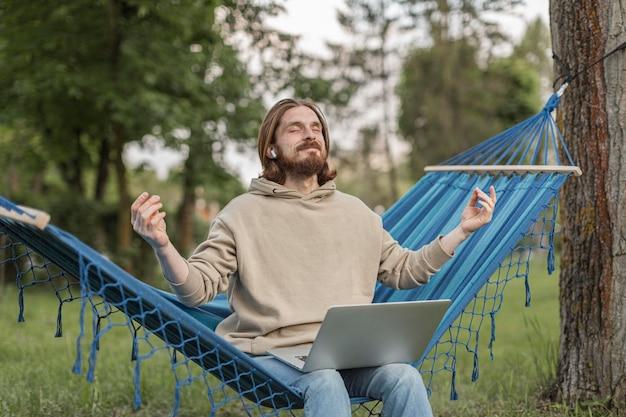 Mens die aan zenmuziek luistert terwijl het zitten op hangmat