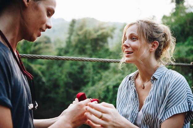 Mens die aan zijn gelukkig meisje in openlucht liefde en huwelijksconcept voorstellen