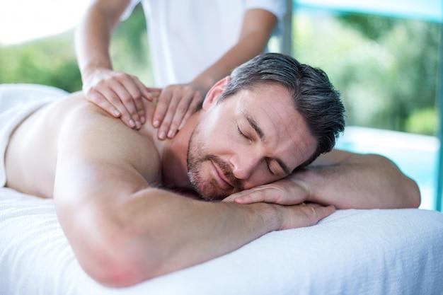 Mens die achtermassage van masseur ontvangt