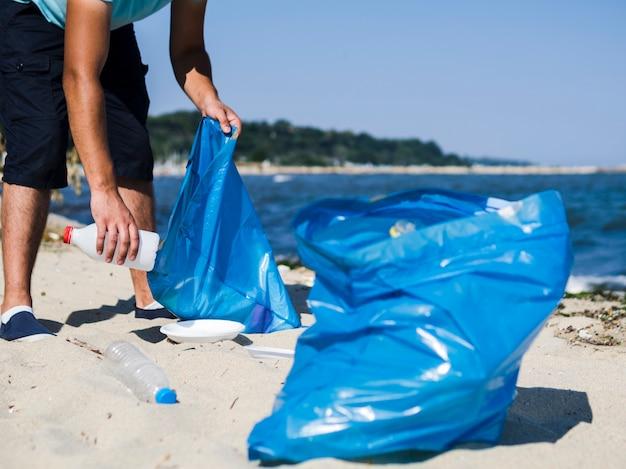 Mens die afval plastic afval van het strand verzamelt en het in blauwe vuilniszak zet