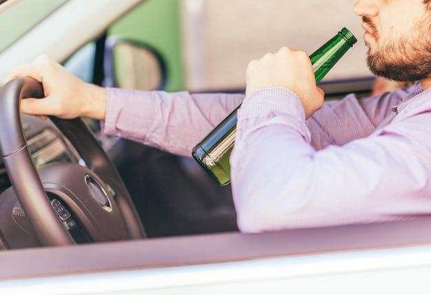 Mens die alcohol drinkt terwijl het drijven van de auto