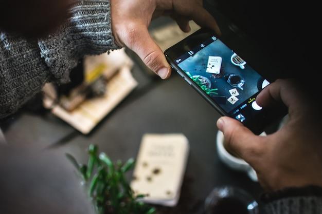 Mens die beeld van koffie en cake met zijn telefoon neemt