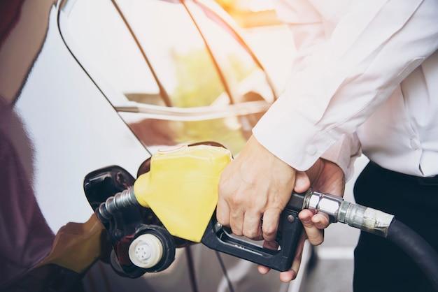 Mens die benzinebrandstof in zijn auto in een pompbenzinestation zet