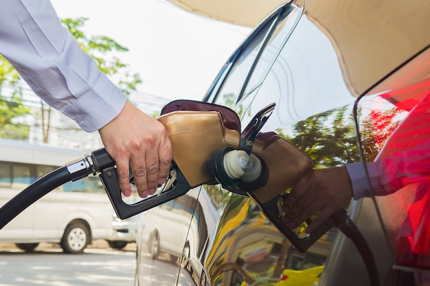 Mens die benzinebrandstof zet in zijn auto in een pompbenzinestation