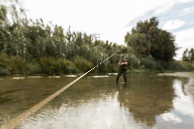 Mens die bij de rivier vist
