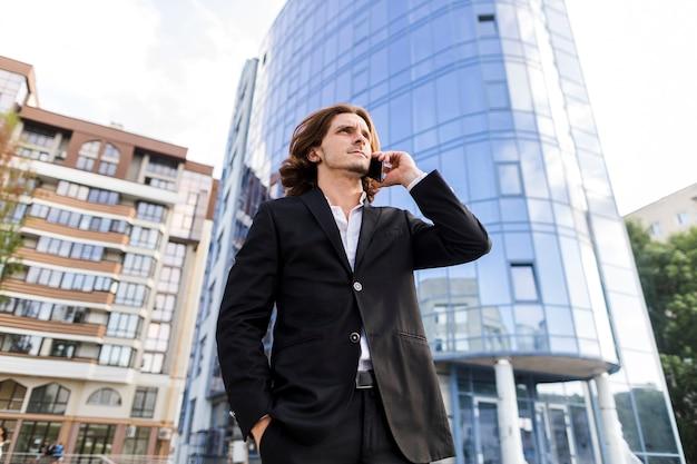 Mens die bij de telefoon voor een gebouw spreekt