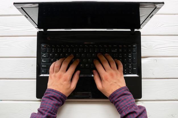 Mens die bij zijn laptop aan witte houten achtergrond werkt
