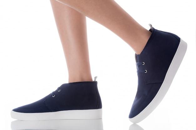Mens die blauw manierschoeisel dragen die met zijprofielmening stappen die op wit wordt geïsoleerd