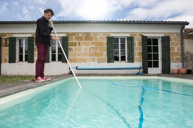 Mens die blauw zwembad met stofzuiger schoonmaakt