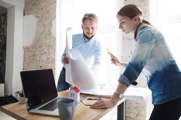 Mens die blauwdruk toont aan zijn vrouwelijke collega's op het werk