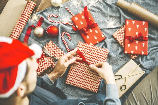 Mens die boog van lint op gift maakt