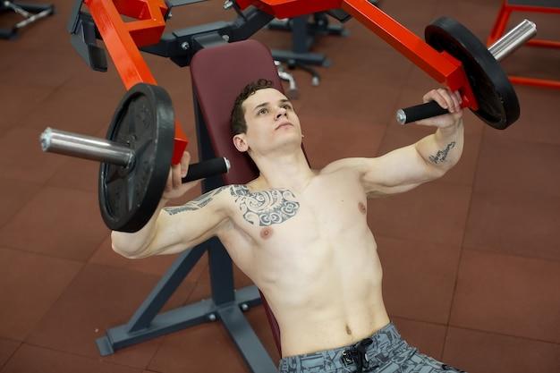 Mens die borstoefeningen op verticale bankpersmachine doet