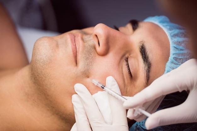 Mens die botox injectie op zijn gezicht ontvangt
