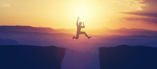 Mens die boven de klip in de bergen springt.