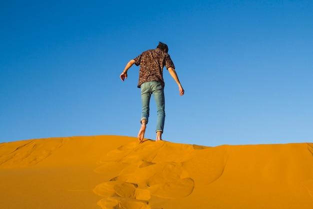 Mens die bovenop duin in woestijn loopt
