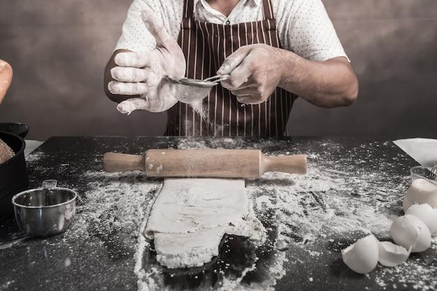 Mens die broodjes voorbereiden bij lijst in bakkerij