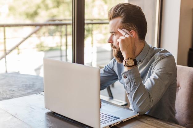 Mens die buitenvenster met laptop op bureau in caf� kijkt