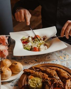 Mens die caesar salade met gemengde ingrediënten eet