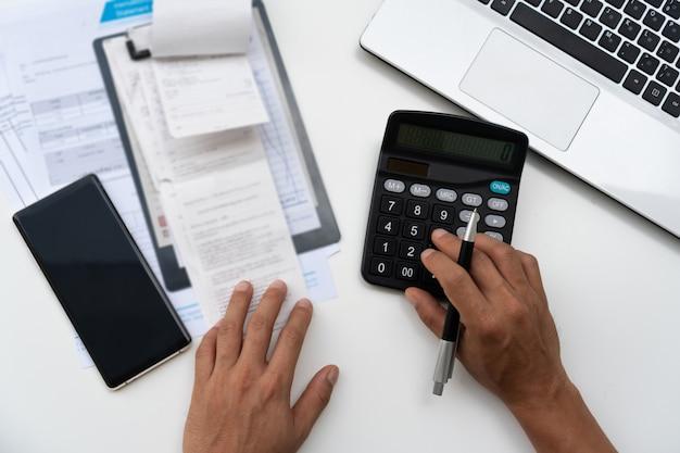Mens die calculator met thuis het doen van financiën gebruiken.