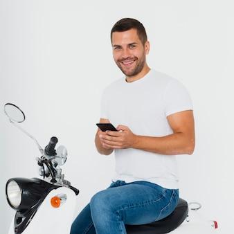 Mens die camera bekijkt en op zijn mobiele telefoon typt