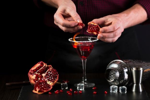 Mens die cocktailglas met granaatappelzaden verfraait
