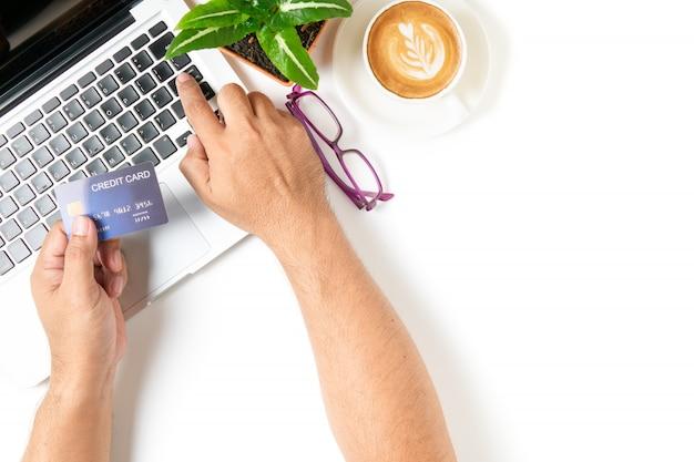 Mens die creditcard voor het online winkelen met de hete koffie van de lattekunst gebruiken die op witte achtergrond wordt geïsoleerd