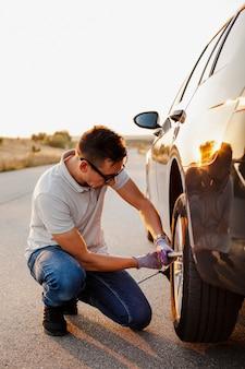 Mens die de bouten van het autowiel aanhaalt
