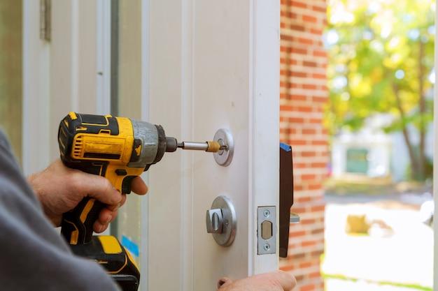 Mens die de deurknop herstelt. close-up van de handen van de werknemer het installeren van nieuwe deur locker