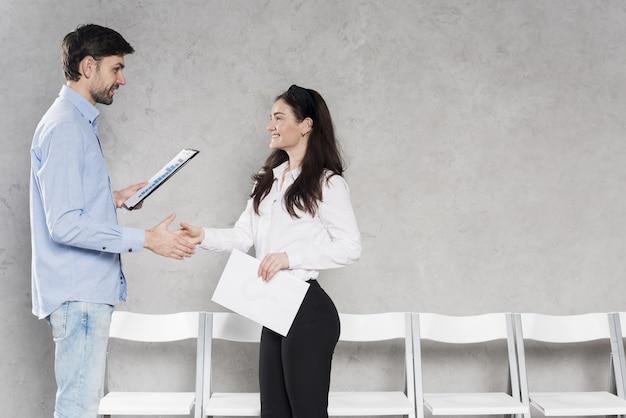 Mens die de hand van de potentiële werknemer schudt vóór sollicitatiegesprek