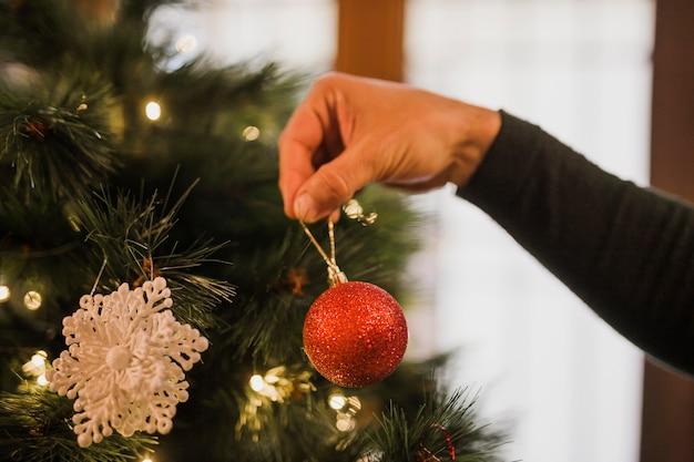 Mens die de kerstboom verfraait