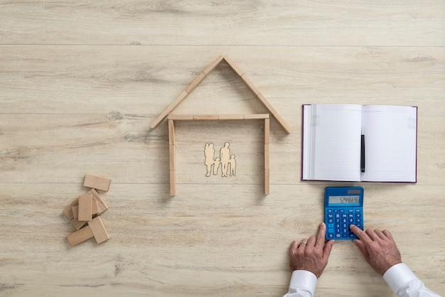 Mens die de kosten van een huis voor familie berekent
