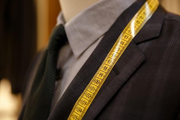 Mens die de maatregelen van zijn kostuum controleert