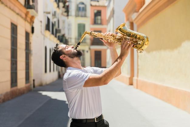 Mens die de saxofoon in straat speelt