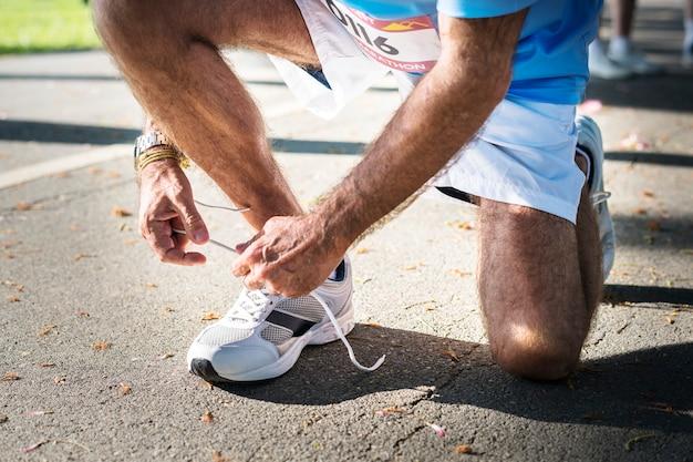 Mens die de schoenveter op zijn schoen bindt