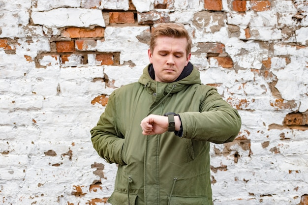 Mens die de tijd controleert op zijn polshorloge. knap jonge mensenverblijf tegen witte en rode oude bakstenen muur, wintertijd