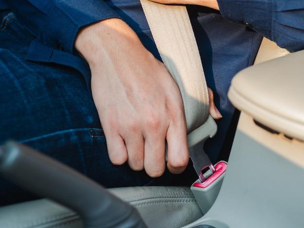 Mens die de veiligheidsgordel in de auto bevestigt