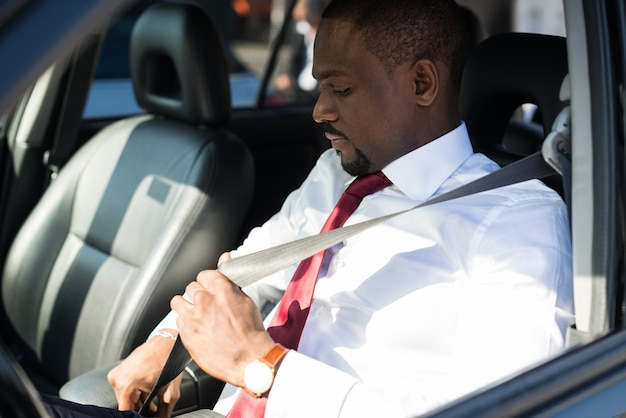 Mens die de veiligheidsgordel in zijn auto bevestigt