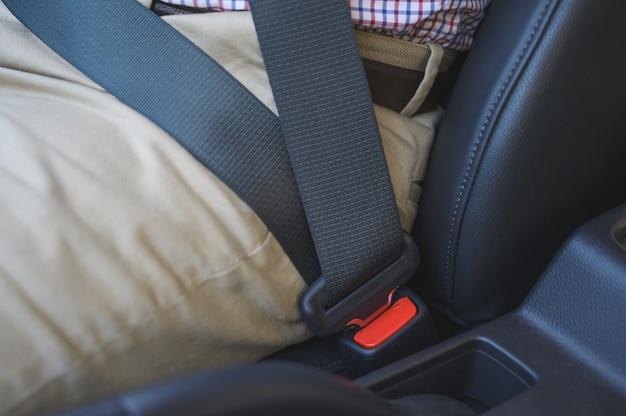 Mens die de veiligheidsgordel in zijn auto zet