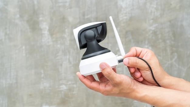 Mens die de veiligheidsip camera met een kabel verbindt