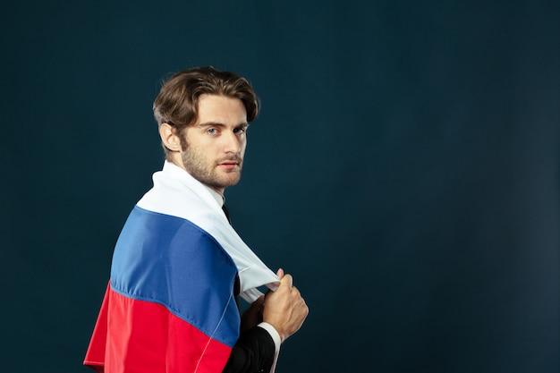 Mens die de vlag van rusland op zwarte achtergrond houdt